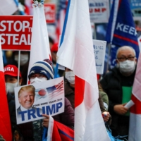 Supporters of U.S. President Donald Trump hold a rally in Tokyo on Wednesday ahead of the inauguration of President-elect Joe Biden. | REUTERS