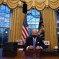 U.S. President Joe Biden prepares to sign a series of orders in the Oval Office of the White House on Wednesday.  | AFP-JIJI