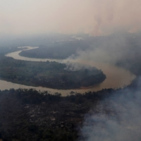 Smoke rises into the air around the Cuiaba river in the Pantanal, the world's largest wetland, in Pocone, Brazil, in August.   REUTERS