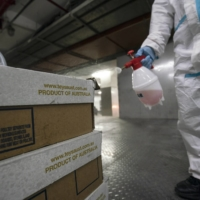 An employee sprays disinfectant on boxes of imported Australian beef at the loading dock of a supermarket in Shanghai on Tuesday. | BLOOMBERG