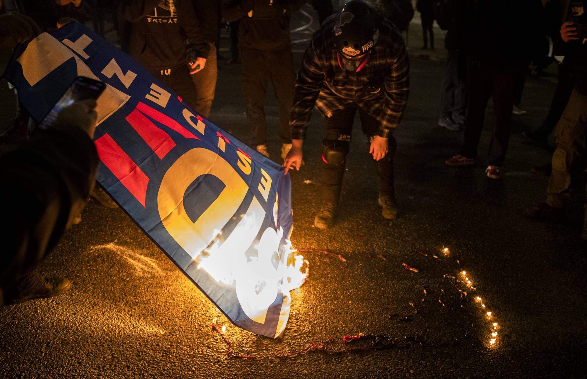Protesters burn a Biden campaign flag in Portland, Oregon, after the inauguration of U.S. President Joe Biden, on Wednesday. | ALISHA JUCEVIC / THE NEW YORK TIMES
