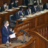 Prime Minister Yoshihide Suga responds to questions during the Upper House plenary session Friday. | KYODO