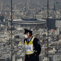 The National Stadium, which will be the main venue for the Tokyo 2020 Olympics and Paralympics, is seen behind a security guard at the Shibuya Sky observation deck in the capital, six months ahead of the international sporting event. | REUTERS