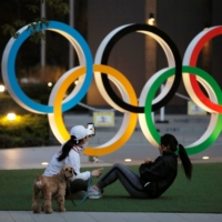 Women work out in front of the Olympic rings near the National Stadium in Tokyo on Friday. | REUTERS