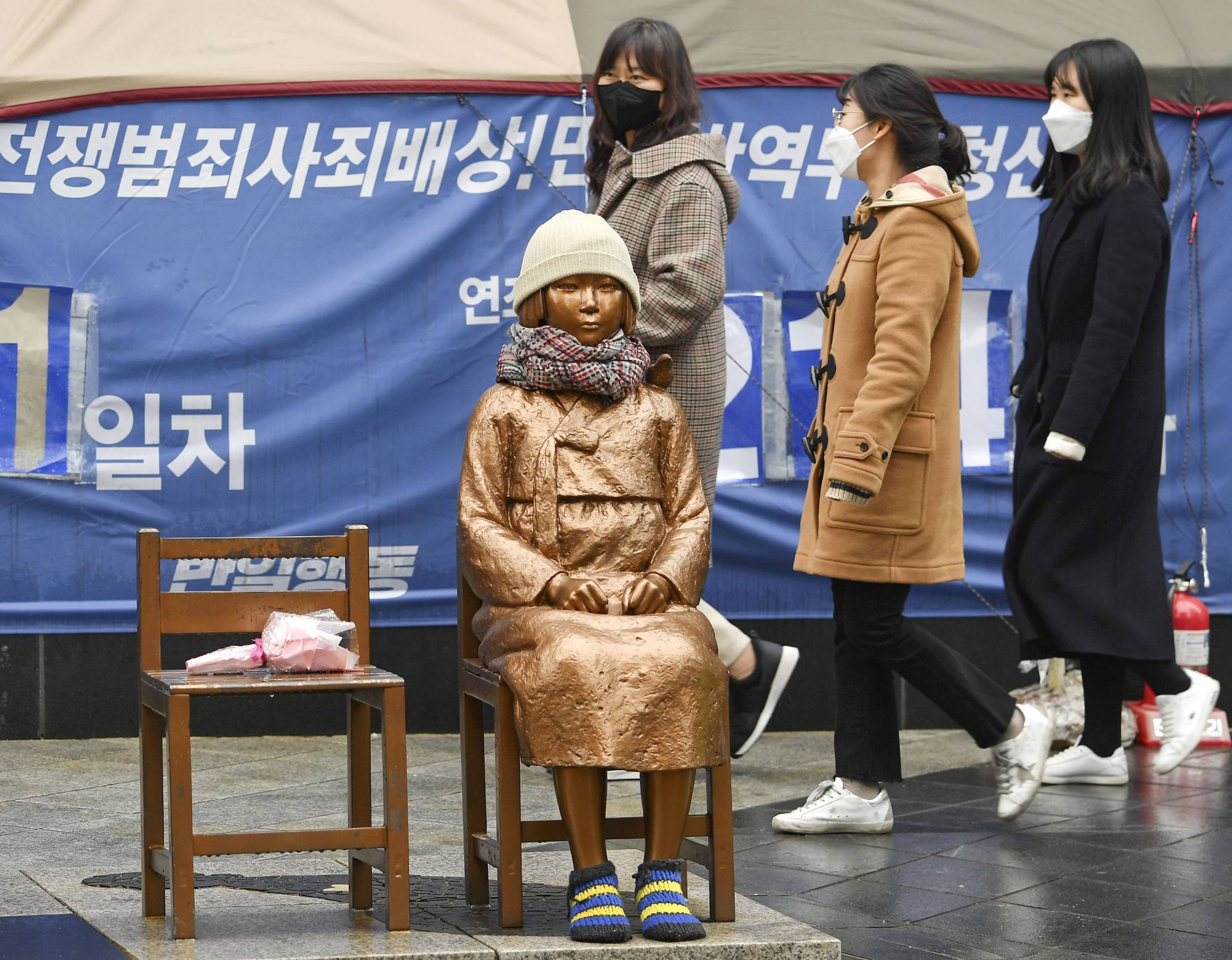 Passersby look at a statue symbolizing the so-called comfort women, who suffered under Japan's military brothel system before and during World War II, in front of the Japanese Embassy in Seoul on Friday. | KYODO