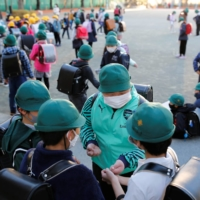 Students gather at an elementary school in Tokyo in December. A Tokyo girl who has never been overseas has tested positive for a variant of the novel coronavirus that is spreading in Britain, according to the health ministry. | REUTERS