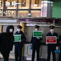 Policemen stand on a street while holding signs asking people to stay home amid rising coronavirus cases in Tokyo, on Friday. | AFP-JIJI