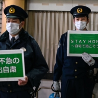 Policemen hold signs asking people to stay home amid rising numbers of coronavirus cases in Tokyo on Friday.