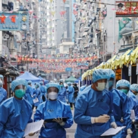 Health workers are seen in protective gear inside a locked-down portion of the Jordan residential area to contain a new coronavirus outbreak in Hong Kong on Saturday. | REUTERS