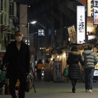 People walk on a street crowded with restaurants and bars in Tokyo's Ueno area Friday. | KYODO
