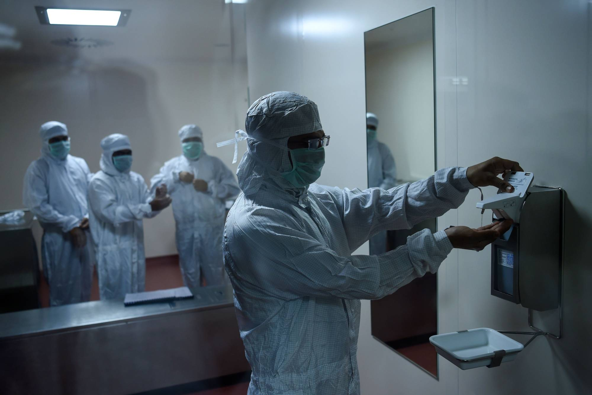 Employees prepare themselves before entering a lab where the Covishield vaccine is being manufactured, at India's Serum Institute in Pune on Friday.  | AFP-JIJI