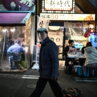 A man wearing a face shield pulls a suitcase along a street in Tokyo on Friday.