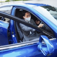 Environment Minister Shinjiro Koizumi sits in a Toyota Motor Corp. fuel-cell vehicle at the Environment Ministry in November. | KYODO
