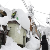 People remove snow from their house and store in Yuzawa, Niigata Prefecture, on Dec. 17. | KYODO