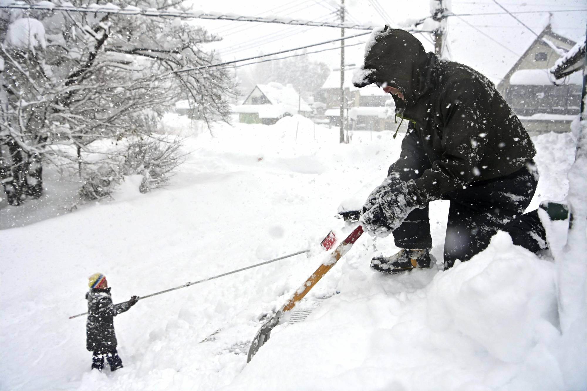 People remove snow from their house in Minakami, Gunma Prefecture, on Dec. 16. | KYODO