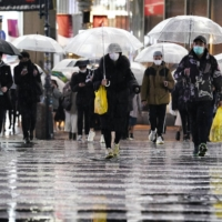 People walk at a scramble crossing near Shibuya Station on Saturday as the country's cumulative death toll linked to the virus topped 5,000. | KYODO