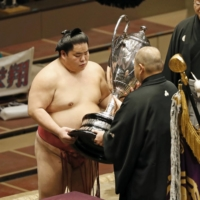 Daieisho is presented with the Emperor's Cup by Japan Sumo Association Chairman Hakkaku after winning the New Year Grand Sumo Tournament on Sunday. | KYODO