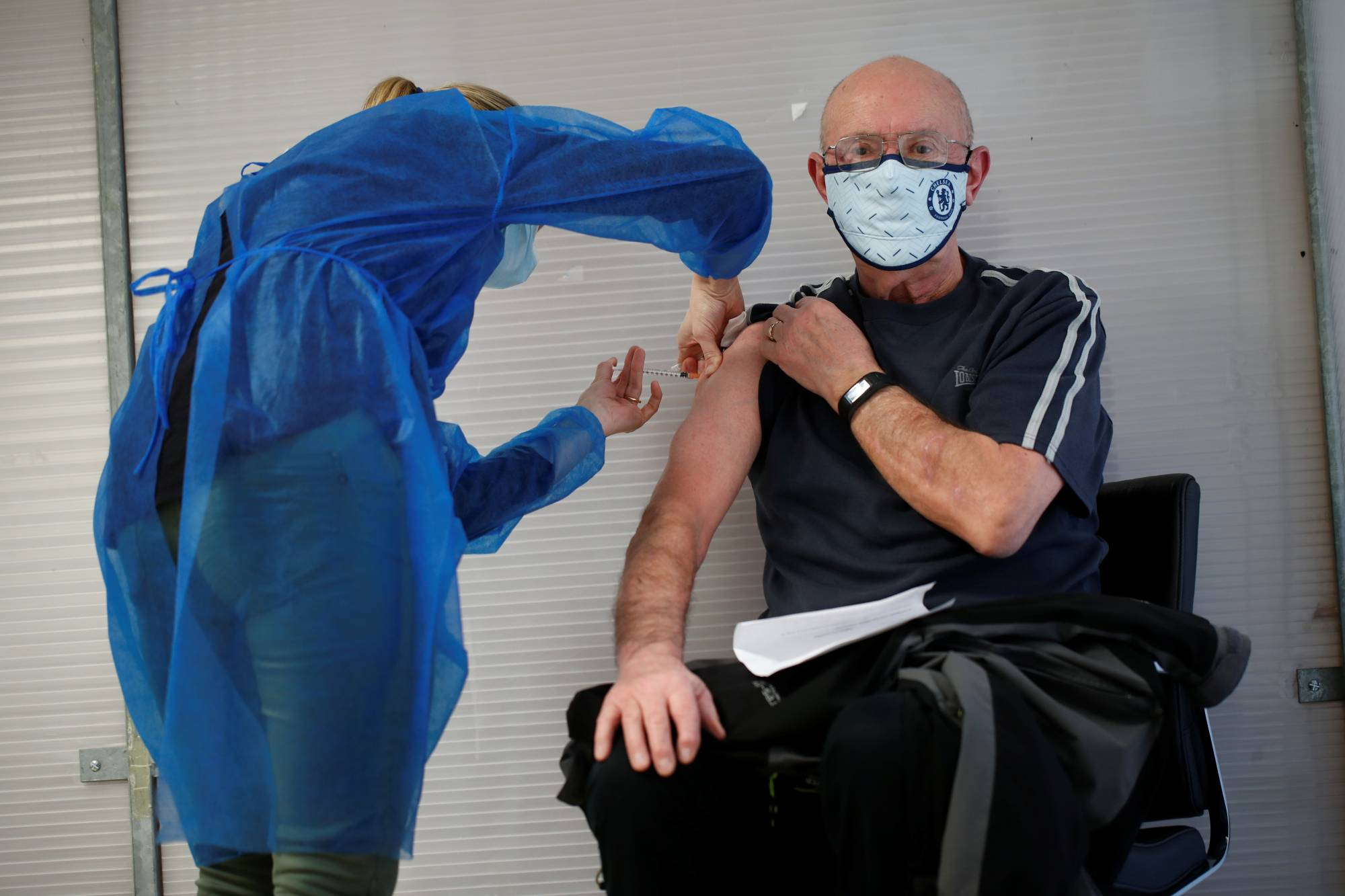 An elderly man  receives a dose of the Pfizer-BioNTech COVID-19 vaccine at a vaccination center in Guingamp, France, on Friday.  | REUTERS