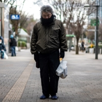 'Yuichiro' holds a bag of food distributed by nonprofit organization Moyai Support Centre for Independent Living, in the Shinjuku district of Tokyo on Jan. 9. | AFP-JIJI