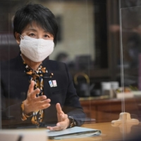 Doubling up on mask protection during a recent interview, Justice Minister Yoko Kamikawa acknowledges the impacts of Japan's border control measures on its international communities and visa applicants. | RYUSEI TAKAHASHI