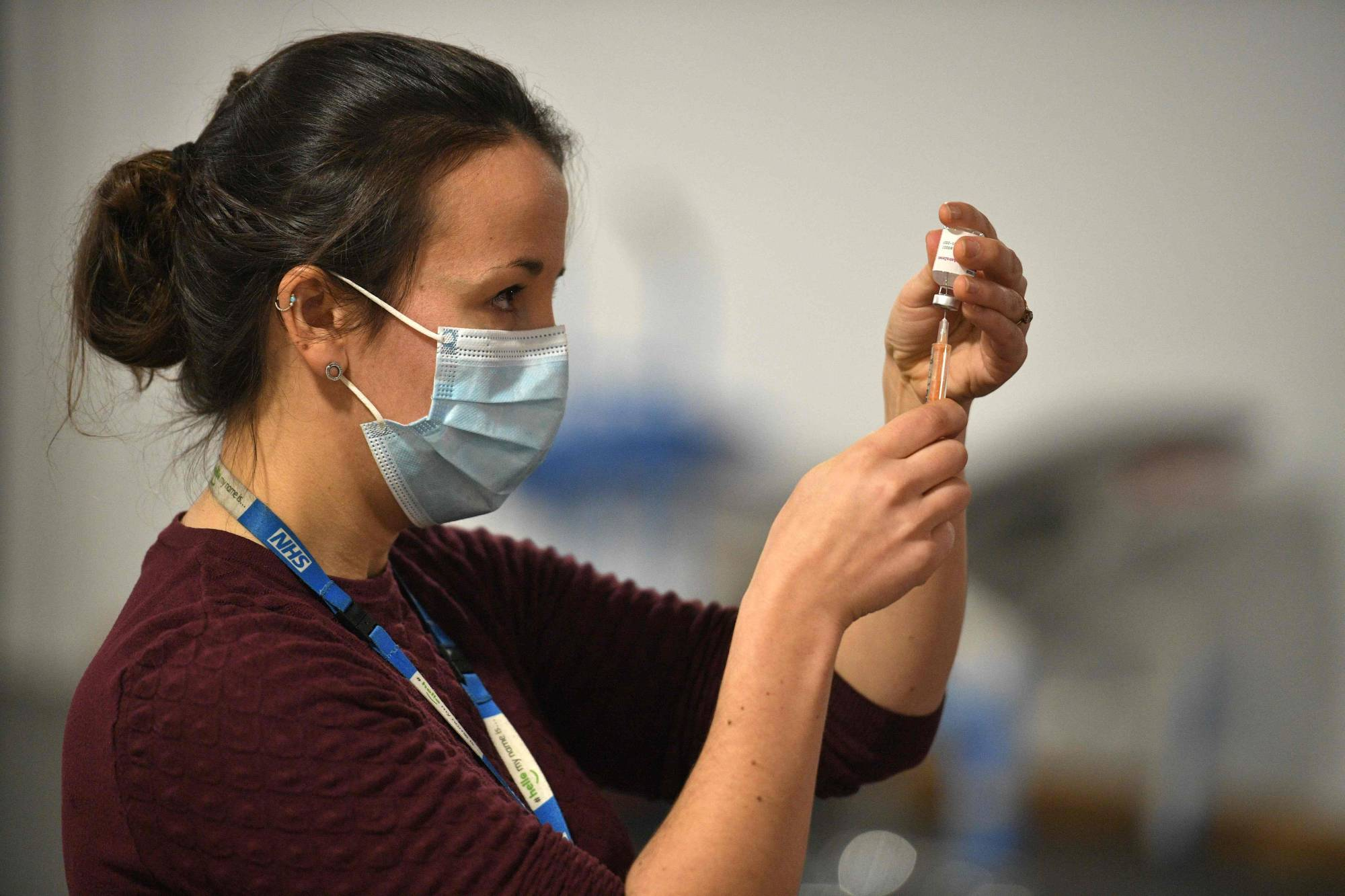 A doctor prepares to administer the Oxford-AstraZeneca COVID-19 vaccine at a temporary vaccination center in the Keepmoat Stadium in Doncaster, England, on Saturday. | AFP-JIJI
