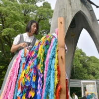 A junior high school student offers paper cranes, a symbol of hope in Japan, at the Children's Peace Monument in the Hiroshima Peace Memorial Park. The monument is modeled after Sadako Sasaki, who died of leukemia 10 years after the 1945 bombing. | KYODO
