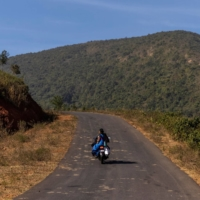 Reena Jani, a health worker, rides on her neighbor's motorcycle as she travels to Mathalput Community Health Center to receive the vaccine developed by Oxford University and AstraZeneca, in Koraput, India, on Jan. 16. | REUTERS