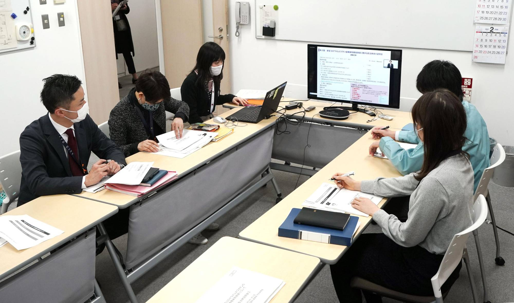 Local health center staff watch the health ministry's online briefing about vaccine rollout plans on Monday in Tokyo. | KYODO