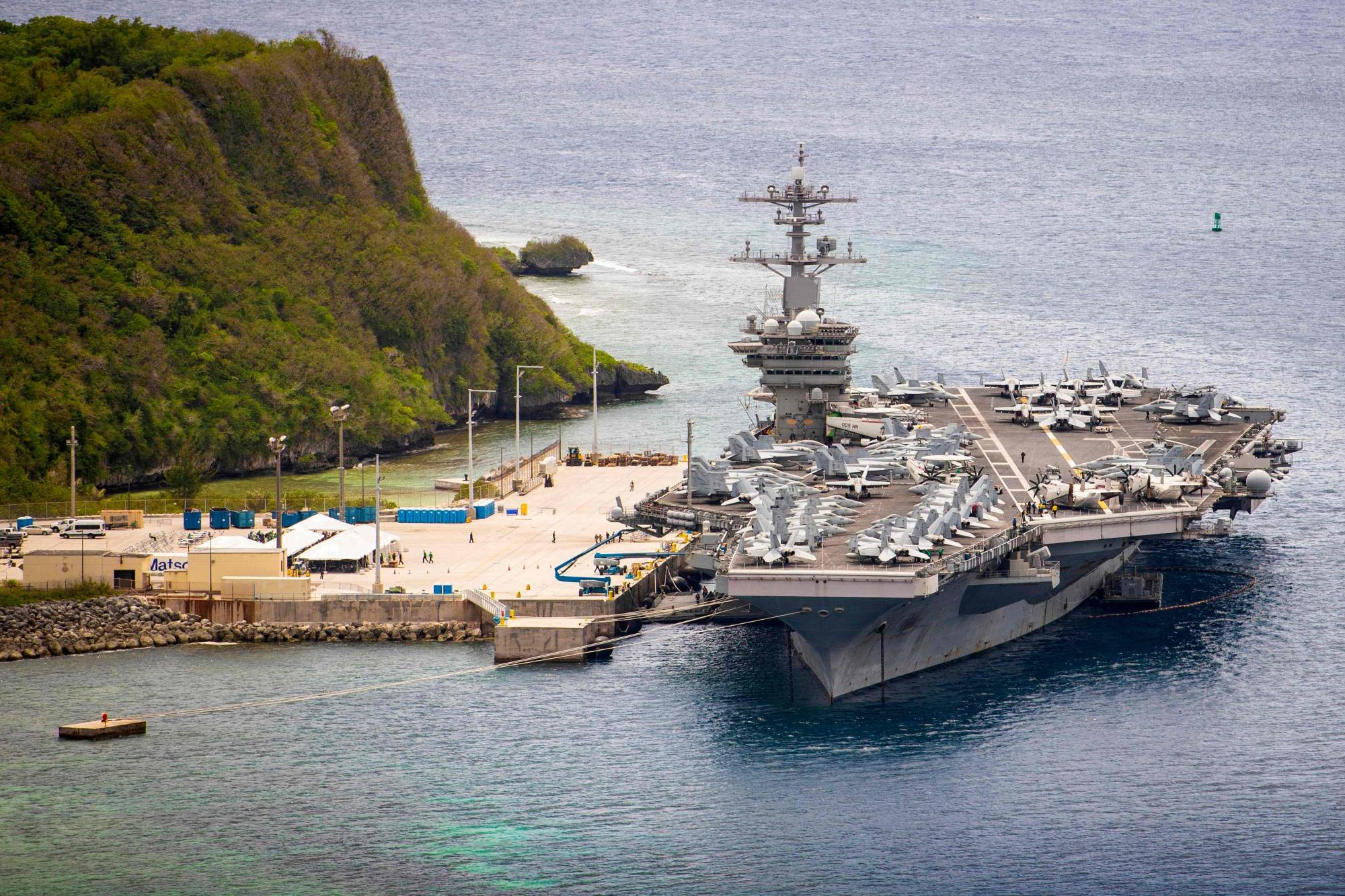The USS Theodore Roosevelt aircraft carrier is moored pierside at Naval Base Guam last May. The carrier's strike group sailed into the South China Sea on a 'freedom of navigation' exercise over the weekend, the first such operation in the region under new U.S. President Joe Biden.  | U.S. NAVY / VIA AFP-JIJI