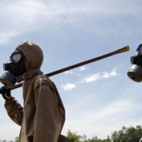 Soldiers in protective gear are pictured after a presentation on detecting unexploded ordnance and defoliant Agent Orange in Vietnam's Da Nang City in June 2011.  | REUTERS