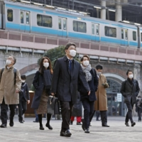 People walk in front of Shimbashi Station in Tokyo on their way to work on Jan. 7. | KYODO