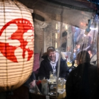 People dine at a restaurant in Tokyo on Friday. A growing number of people in the Japanese government and ruling party believe it will be necessary to extend the coronavirus state of emergency for Tokyo and other parts of the country.