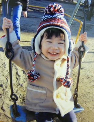 Kosuke, who died after malpractice at Tokyo Women's Medical University Hospital at age 2 in February 2014 and whose family name is being withheld, smiles on a swing in December 2013. | COURTESY OF KOSUKE'S FAMILY / VIA KYODO