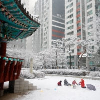 Children play during a heavy snowfall in Seoul on Jan. 12.  | REUTERS