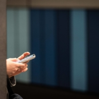 An office worker uses a smartphone on a station platform during morning rush hour in Frankfurt, Germany, in 2019. European lawmakers voted last week for the creation of new legal rights for employees to switch off from work-related tasks and electronic communication outside of office hours without facing consequences. | BLOOMBERG