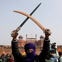 A farmer holds swords during a protest in New Delhi on Tuesday. | REUTERS