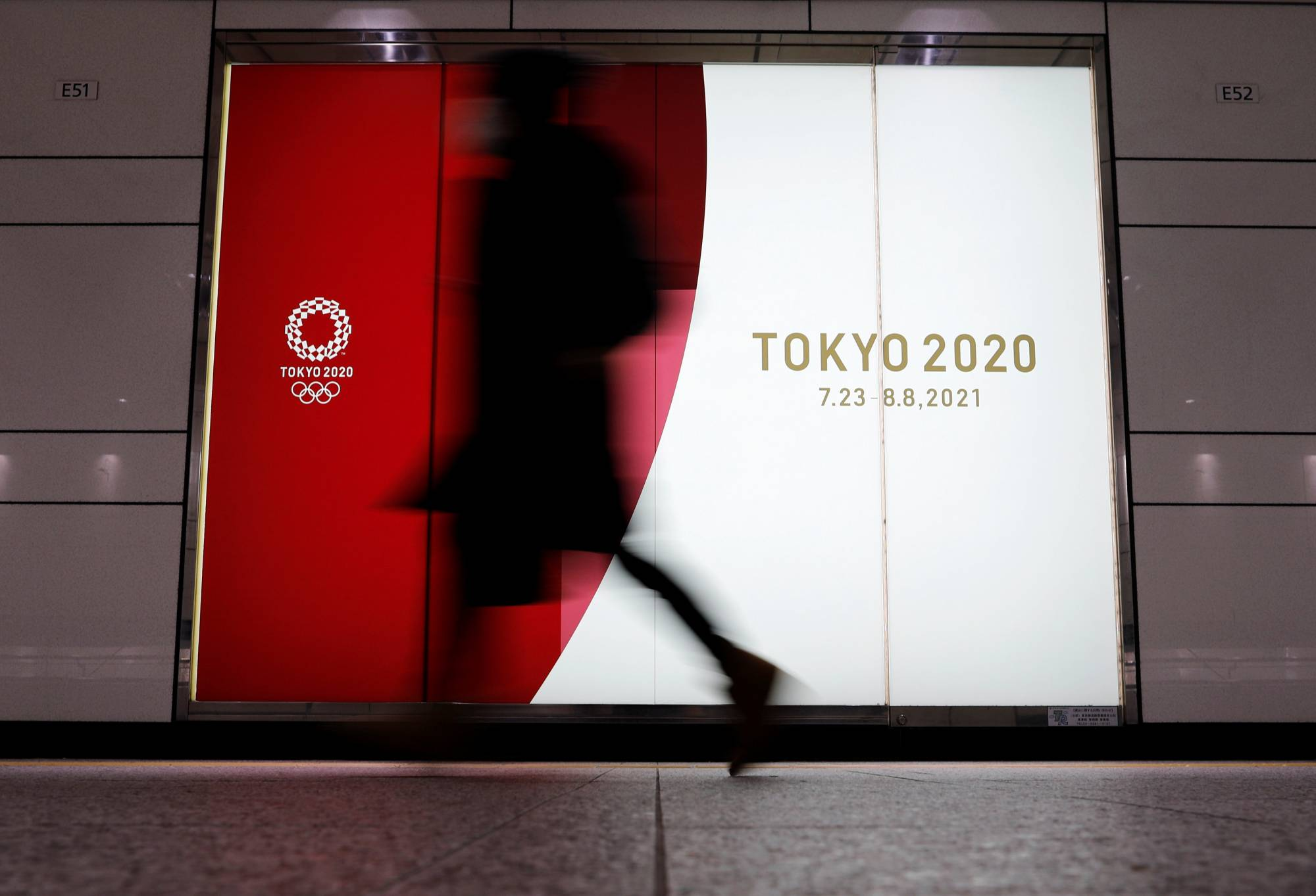 A person walks past an advertisement for the 2020 Tokyo Olympics on Jan. 22.  | REUTERS