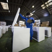 An employee of fridge manufacturer Kanou Reiki checks deep freezers which will be used to store COVID-19 coronavirus vaccines, at the company's warehouse in Sagamihara, Kanagawa prefecture on Tuesday. | AFP-JIJI