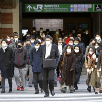 People walk to work near Tokyo Station on Jan. 8, a day after the government issued a fresh state of emergency. | KYODO
