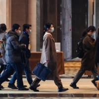 Chinese officials arrive for meetings with the World Health Organization team investigating the origins of the COVID-19 pandemic, at the Hilton Wuhan Optics Valley Hotel in Wuhan, China, on Friday. | AFP-JIJI