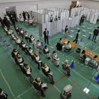Social distancing measures are taken, with partitions set up to separate participants, during a coronavirus vaccination simulation held at a university gymnasium in Kawasaki on Wednesday. | KYODO