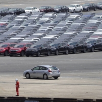 Vehicles bound for shipment sit parked at a port in Yokohama in July. The auto sector showed a strong recovery from June and contributed to overall gains in industrial output, but its upward momentum eased in November and December. | BLOOMBERG