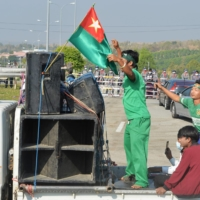 Supporters of the military-aligned opposition Union Solidarity and Development Party protesting election results ride a motorcade past a police barricade along a road in Naypyidaw, Myanmar, on Friday, ahead of the reopening of the parliament on Tuesday. | AFP-JIJI