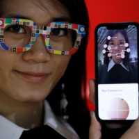 An employee of online fashion retailer Zozo Inc. poses with 'Zozoglass' and its smartphone application, used to measure skin tone for ordering cosmetics online, during a demonstration at the company's office in Tokyo on Thursday. | REUTERS