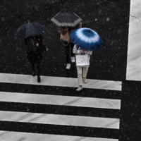 People use umbrellas to shield themselves from rain and snow while crossing a street in Tokyo on Friday. | AFP-JIJI