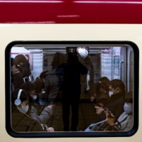 Commuters travel on a train in Tokyo on January 15. Only around 37% of firms in the prefectures under Japan's current state of emergency have met the government's target of cutting commuters by 70% or more. | AFP-JIJI