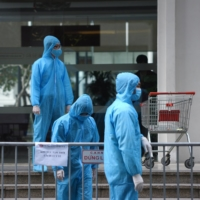 Medical workers in protective suits stand outside a quarantined building amid a fresh coronavirus  outbreak in Hanoi on Friday. | REUTERS