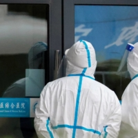 Staff members in protective suits stand at Hubei Provincial Hospital of Integrated Chinese and Western Medicine, where members of the World Health Organization (WHO) team tasked with investigating the origins of the coronavirus were visiting, in Wuhan, China, on Friday. | REUTERS
