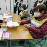 Documents are checked during a vaccination simulation held in Kawasaki on Wednesday. | KYODO
