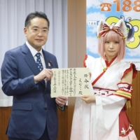Shinji Inoue, minister in charge of Cool Japan strategy, hands a letter to cosplayer Enako that names her as Cool Japan ambassador, in Tokyo in December. | KYODO
